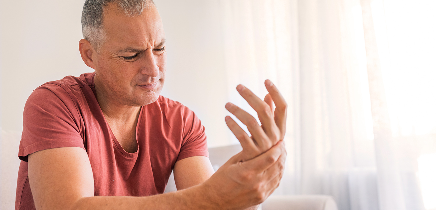 Man experiencing pain in his left hand