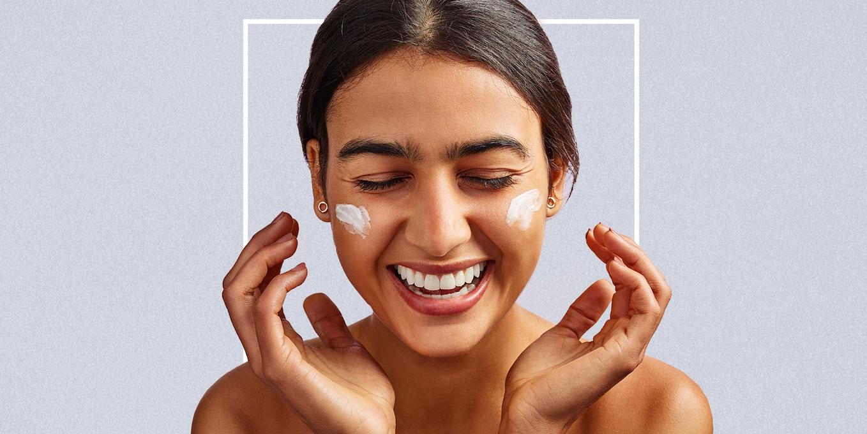 Girl smiling while applying cream
